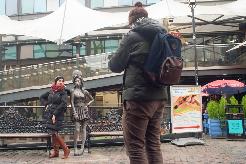 A tourist poses with the bronze statue of Amy Winehouse in Stables Market